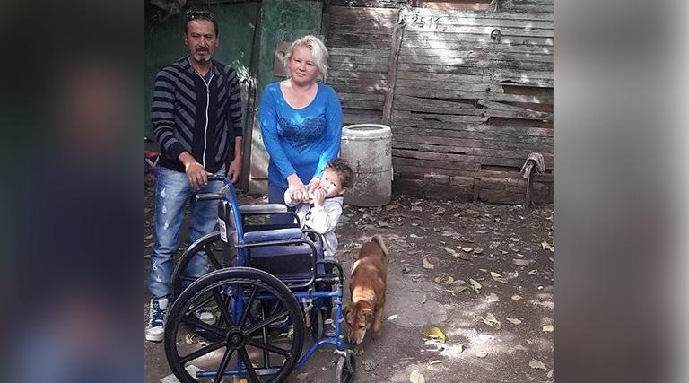 Claudia (derecha) recibe conforme la silla de ruedas por parte de Juan.